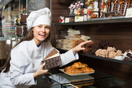 Young shopgirl posing with delicious chocolate and confectionery at display Stock Photo