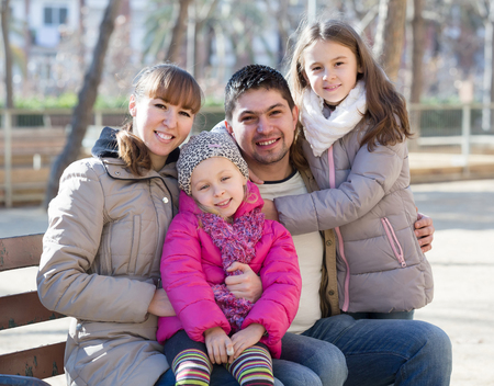 Happy family with two girls outdoors in sunny fall day