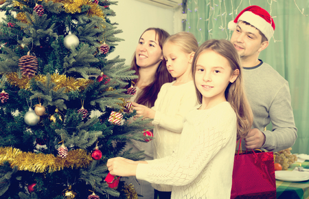 home decorating: Happy parents with two children decorating Christmas tree at home