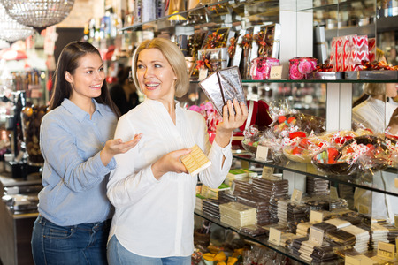 filled: Female friends selecting bars of fine chocolates at coffee-house