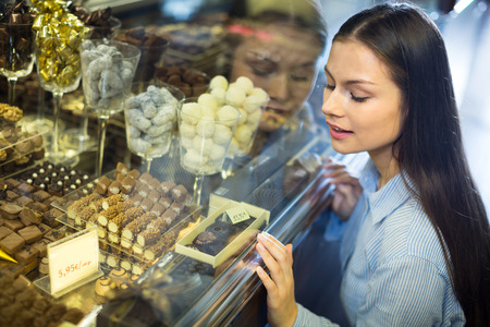 woman selecting fine chocolates and confectionery at cafe display