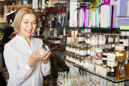 selecting: Mature woman selecting natural honey at coffee-house display