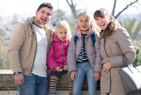 Portrait of joyful ordinary family with two little daughters in city at sunny day