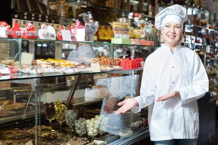with fillings: Happy woman selling chocolates with praline and other fillings Stock Photo