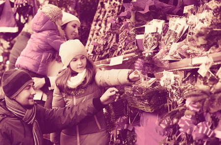 4s: Family of four choosing floral christmas decorations at market together
