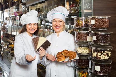 saleswomen: Happy saleswomen offering  delicious chocolate and confectionery
