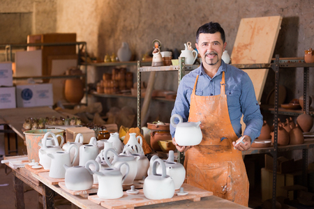 atelier: Sculptor man standing in atelier and holding white clay teapot