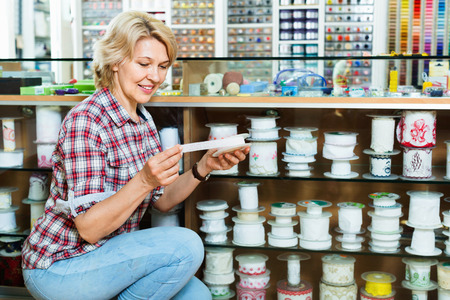 glad: Mature glad smiling woman customer picking various ribbon in sewing department