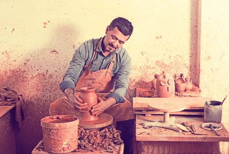 Happy elderly man making pot using pottery wheel in studio