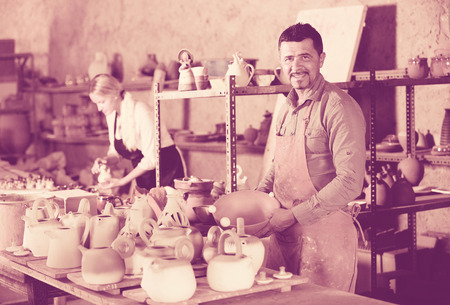artisans: mature and young artisans taking ceramics in hands and standing in workshop