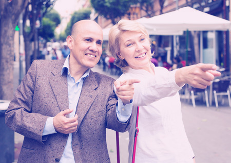 closeup of cheerful retiree man and woman having a walk and pointing with finger in city