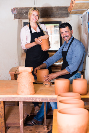 two wheel: portrait of two cheerful smiling potters working with ceramics and pottery wheel in atelier. Focus on woman