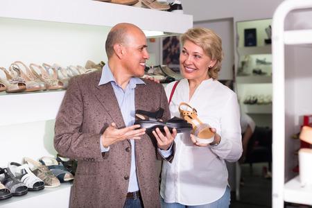 familias felices: retrato de alegre sonriente hombre maduro y una mujer recogiendo par de zapatos en Boutique