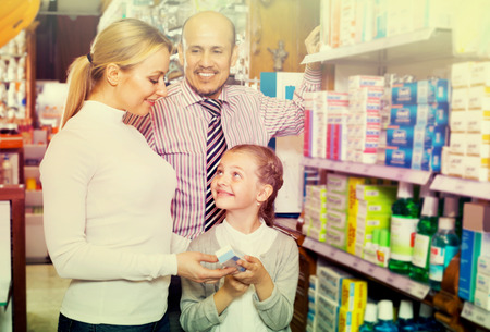three persons: caucasian family of three persons choosing items in the pharmacy