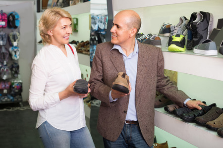 retirees: Two smiling russian retirees together choosing pair of shoes for men in shoe store