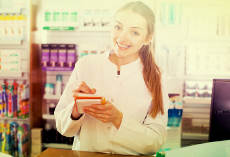 farmacy: Portrait of cheerful young female pharmacist working in modern farmacy Stock Photo