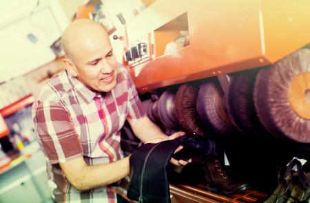 cobbler: cobbler polishing shoes on service machine at footwear shop