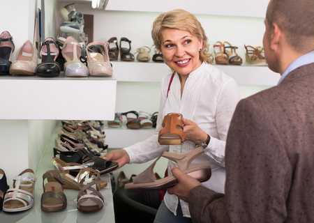 retirees: Two smiling european  retirees together choosing pair of shoes in fashion store