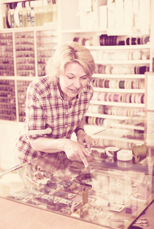 sewing supplies: smiling  elderly woman choosing sewing supplies in glass showcase in boutique