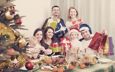 granny and grandad: Smiling Mature parents with adult kids and grandchildren celebrating Merry Christmas
