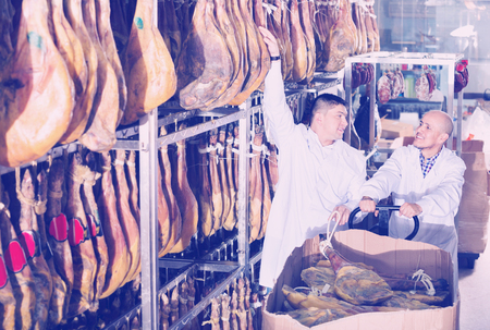 technologists: Smiling positive butchery technologists in white gown checking joints of iberico jamon Stock Photo