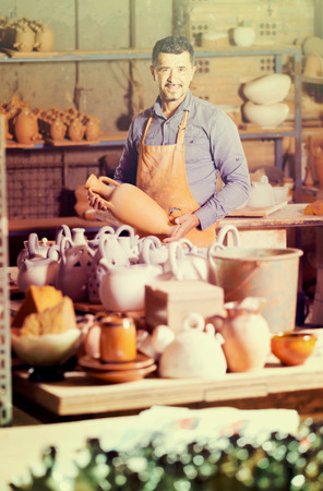 atelier: happy european man potter holding ceramic vessels in atelier
