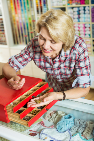 clasps: Woman picking buttons and clasps from container in craft shop