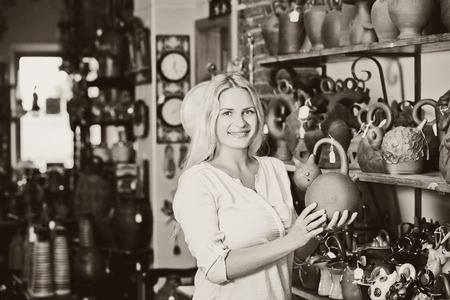 a jar stand: Smilling woman selecting black ceramic pot in atelier