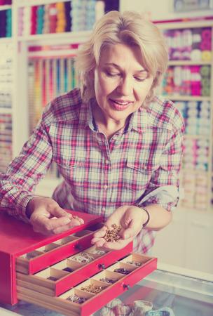 clasps: joyful smiling mature woman customer choosing various metallic clasps in sewing store counter Stock Photo
