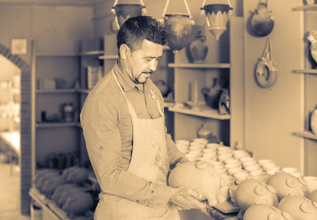 russian man: Smiling russian man potter holding ceramic vessels in atelier