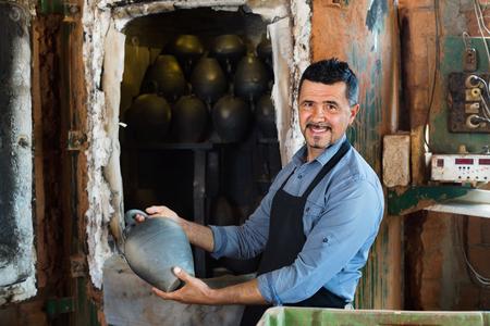 diligente: Alegre artesano diligente amigable llevar recipiente esmaltado negro recién hecho en el taller de cerámica
