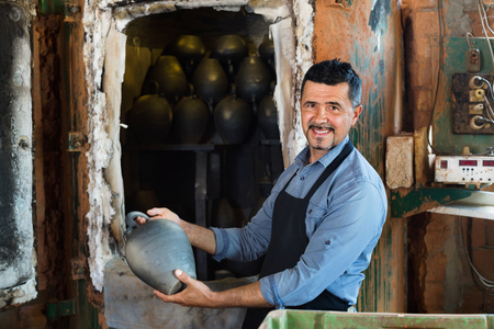 diligent: Cheerful friendly diligent craftsman carrying fresh baked black glazed vessel in ceramics atelier