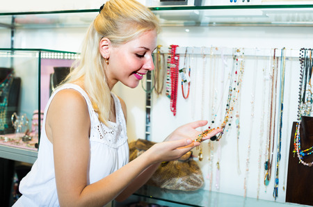 personal shopper: ?Young smiling woman shopping necklace in bijouterie boutique