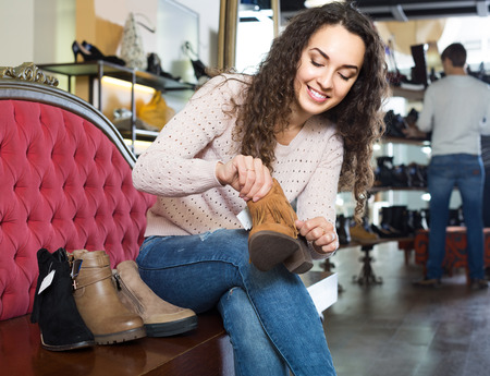 comprando zapatos: positive russian female buying winter female shoes in  shoe store Foto de archivo