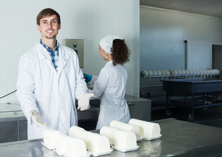 lab coats: Smiling young man and woman in lab coats and gloves on the manufacture