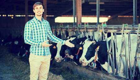 stroking: Cheerful young man happily stroking cows on the farm