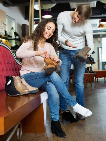 buying shoes: Positive  couple buying winter shoes in a shoe store