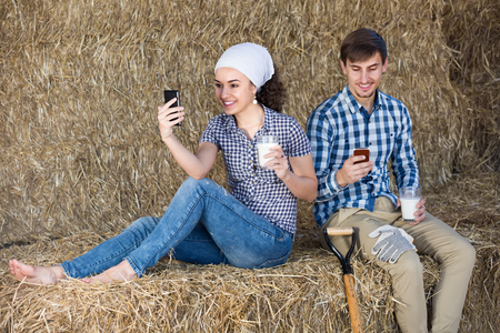 seasonal worker: Young merry man and woman sitting together in the hay and looking in their mobile phones