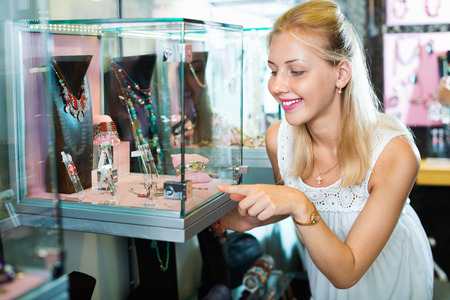 personal shopper: Portrait of young woman standing next to glass showcases in shop with bijouterie