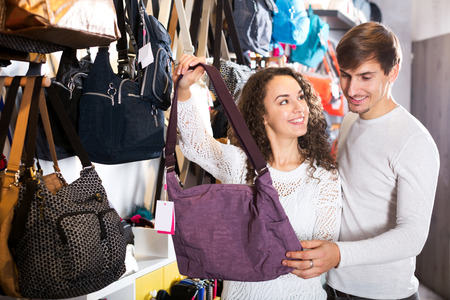 shopgirl: Smiling female shopgirl helping adult man to select handbag in store Stock Photo