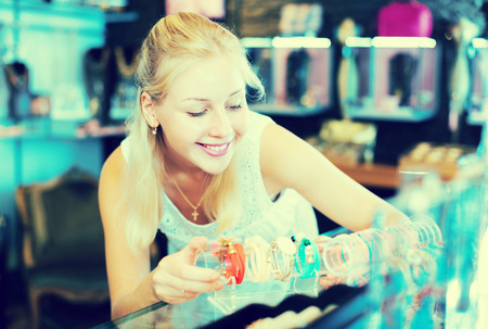Young blonde woman buying bracelet in bijouterie store