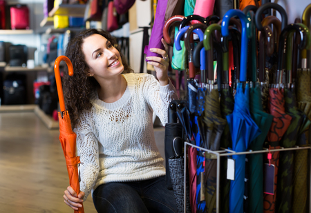 haberdashery: Young woman purchasing automatic umbrella in haberdashery shop Stock Photo