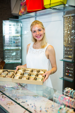 ?Young smiling woman seller showing various bracelets in jewellery boutique Stock Photo