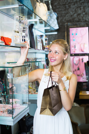 personal shopper: Young cheerful woman picking earrings in jewellery boutique Stock Photo