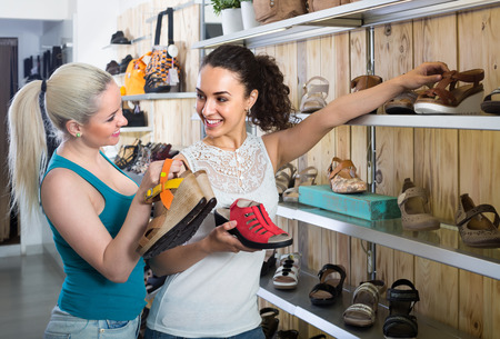 Two cheerful smiling girls selecting new summer sandals in the fashion shoes store Stock Photo