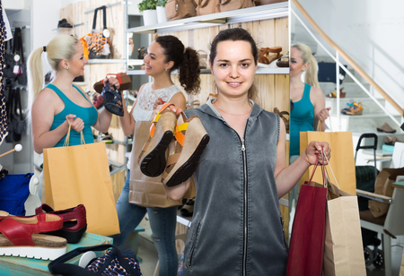 desires 25: three smiling young european girls holding a paper shopping bags in the boutique