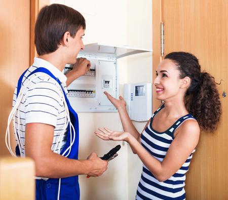 electric meter: Mujer hermosa y reparador cerca de medidor eléctrico en el interior doméstico Foto de archivo