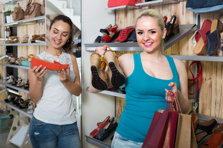 cheerful  customer showing a chosen pair of shoes while her friend still choosing Stock Photo