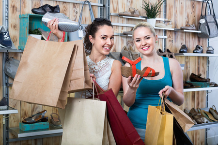 desires 25: Two smiling beautiful happy young girls holding a paper shopping bags in the boutique