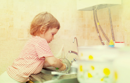 1 2 years: Baby girl  washes dishes in kitchen